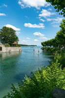 healthy active outdoor couple enjoys paddleboarding on the canals of Lake Constance on a beautiful summer day