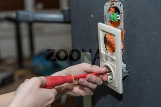 Installieren von Steckdose an der Wand mit Schraubendreher - Nahaufnahme Facharbeiter