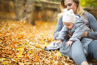 Mother and her little daughter play cuddling on autumn walk in nature outdoors