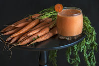 Carrot smoothie glass and bundle of carrots