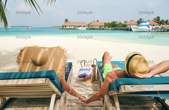 Couple at beach on wooden sun bed loungers