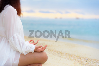 Asian young woman practicing yoga on the beach