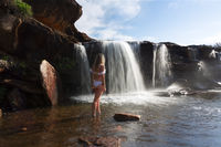 Female exploring and enjoying waterfalls and rock pools in nature