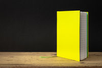 a yellow green note book on a wooden table