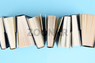 High angle image of a row of books standing on end on a light blue background