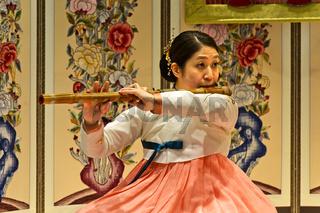Frau musiziert auf der traditionellen Daegeum Querflöte aus Bambus