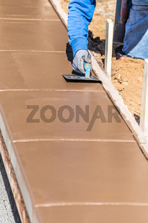 Construction Worker Using Stainless Steel Edger On Wet Cement Forming Coping Around New Pool