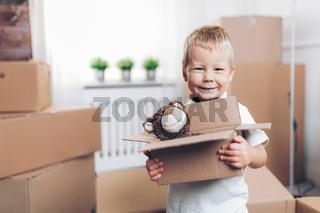 Cute toddler helping out packing boxes and moving