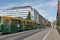 Downtown street and area with a green public tram in Helsinki, Finland