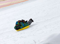 Snow tubing on ski resort at sun day in snowy mountains