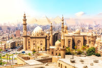 The Mosque-Madrassa of Sultan Hassan and the Pyramids on the background, beautiful view of Cairo, Egypt