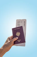 Passport and Air ticket hold by woman blue background
