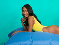 Bright summer portrait of beautiful smiling woman in swimsuit over bright blue screen background