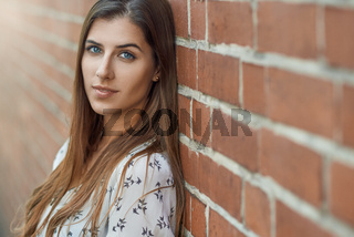 Portrait of young pretty woman near brick wall