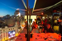 People enjoying evening drinks and amazing panoramic views of Madrid at dusk on rooftop bar of El Corte Ingles department store in Madrid, Spain.