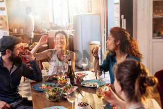 Mixed group of friends having fun while sharing a meal