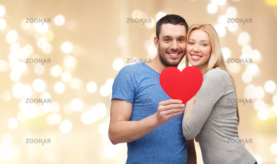 happy couple with red heart over festive lights