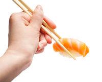 wooden chopsticks hold nigiri sushi with salmon