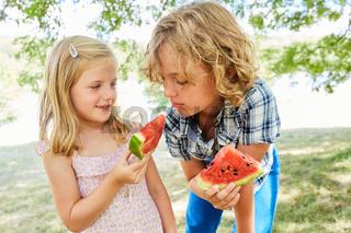 Mädchen gibt ihrem Bruder ein Stück Melone