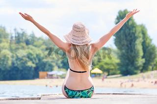 Junge Frau im Bikini mit ausgestreckten Armen