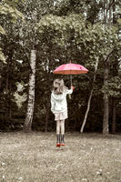 Young girl jump with umbrella