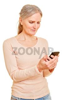 Seniorin liest Textnachricht auf Smartphone