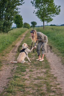 Loving young woman offered a paw by her dog