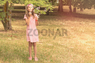 Child girl playing with soap bubbles