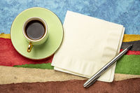 napkin, pen and a cup of coffee