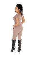 Woman standing in profile in beige jumpsuit