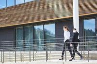 Zwei Geschäftsleute in Eile vor dem Bürogebäude