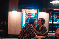 Young couple at the bar, street of the night city