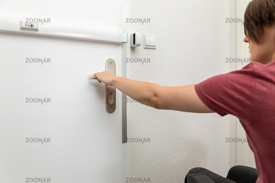 disabled woman opens the door to her flat