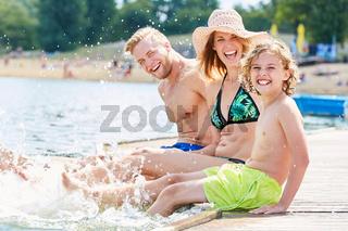 Eltern mit Sohn am Meer spritzen mit Wasser