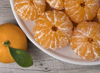 Fresh ripe peeled tangerine in a dish on a wooden background.  Close up view.