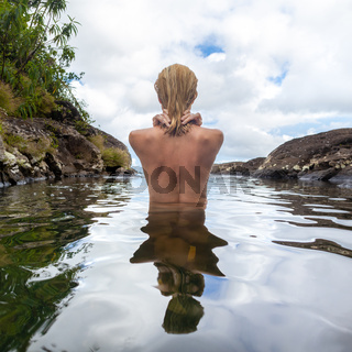 Naked woman bathing and relaxing in natural swimming pool.