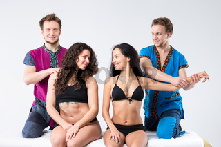 Theme massage and body care. Two brother Caucasian man in uniform make massage of hands and shoulders two beautiful sexy European women in underwear sitting on massage table isolated white background