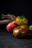 Heirloom tomatoes. Three tomatoes of different colors and a beautiful snag on a black background.