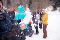 young people measuring the height of finished snowman