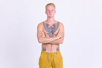 Young blonde shirtless man with tattoos crossing arms