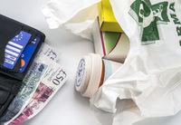 European health insurance card in a wallet along with several pounds sterling and medicines in a bag, concept of medical increase in the crisis of the brexit, conceptual image, horizontal composition