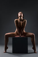 Gorgeous nude women sitting on a cube in the dark