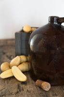 vintage moonshine jug on a rustic wooden table with potatoes and corn cob cork