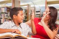 Hispanic Young Boy and Famle Adult High Five Whilte Studying At Library