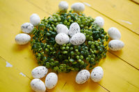 Green decorative Easter quail eggs wreath on yellow wooden table