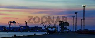 Silhouetten der Maschinen und Gebäude im Hafen von Rostock bei Sonnenuntergang