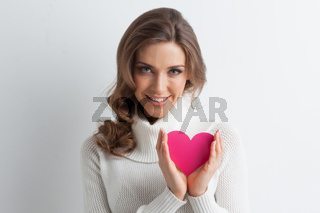 Smiling woman with paper heart