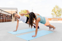 women making high five in side plank on sport mats