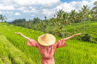 Relaxed fashionable caucasian woman wearing red asian style kimono and traditional asian paddy hat, arms rised to sky, enjoying pure nature at beautiful green rice fields on Bali island