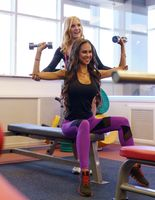 Girl helps her friend to workout with dumbbells